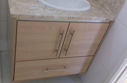Gabinete sob medida para banheiro com puxadores de ferro.